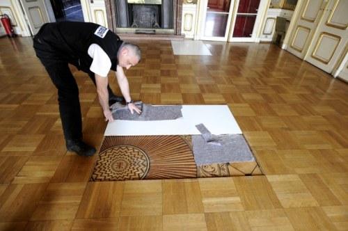 Ein Sicherheitsmann zeigt den originalen Intarsienboden, der unter dem neuen Parkett liegt (Foto: Corn)